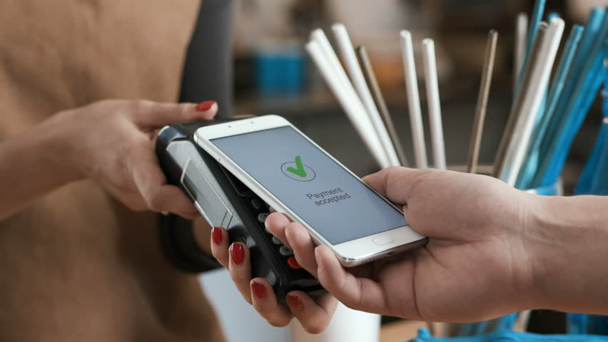 Female employee near cash desk of restaurant store for breakfast or lunch. Nfc cellhone of male buyer with cashless wallet of e-money for pos card reader and checkout. Morning life of caucasian people | Shutterstock HD Video #1009429502