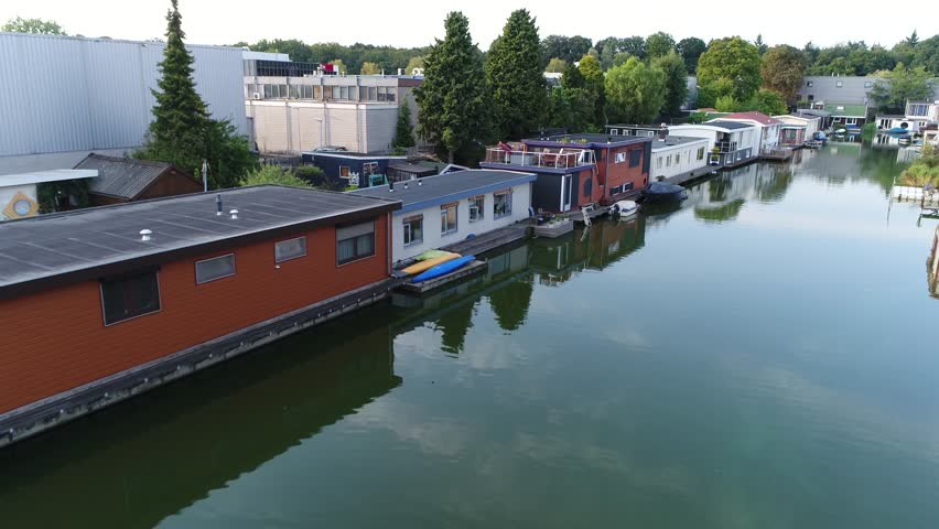 Aerial bird view footage of houseboats that has been designed and modified to be used primarily as a home these houseboats are not motorized because they are moored kept stationary at a fixed point 4k