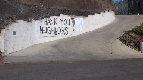 VENTURA, CALIFORNIA - CIRCA 2017 - A thank you to neighbors is spray painted on a wall outside a house during the devastating Thomas Fire.