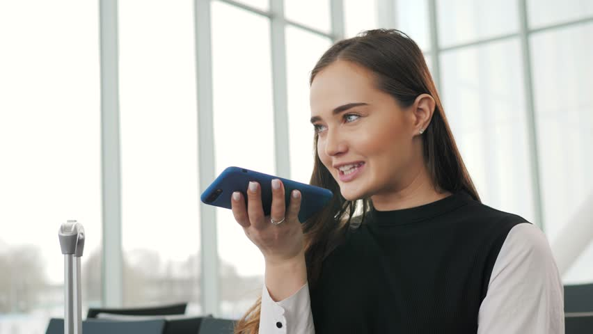 Portrait of a girl using the voice recognition of the phone and looking at cell phone near airport terminal in hotel on vacation tourist speech personal assistant natural language user interface