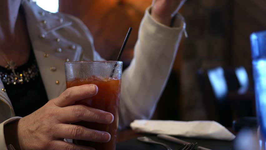 A middle aged woman drinks a bloody mary alcoholic beverage in bar