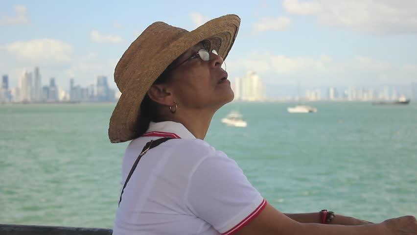 Panama City, Panama - February 28, 2018: Mature Latina woman wearing straw  hat enjoying the view to Panama bay