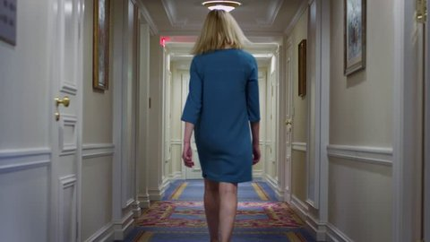 Young woman in blue dress walking along hallway corridor at cozy hotel. Woman walking on long corridor in home interior back view