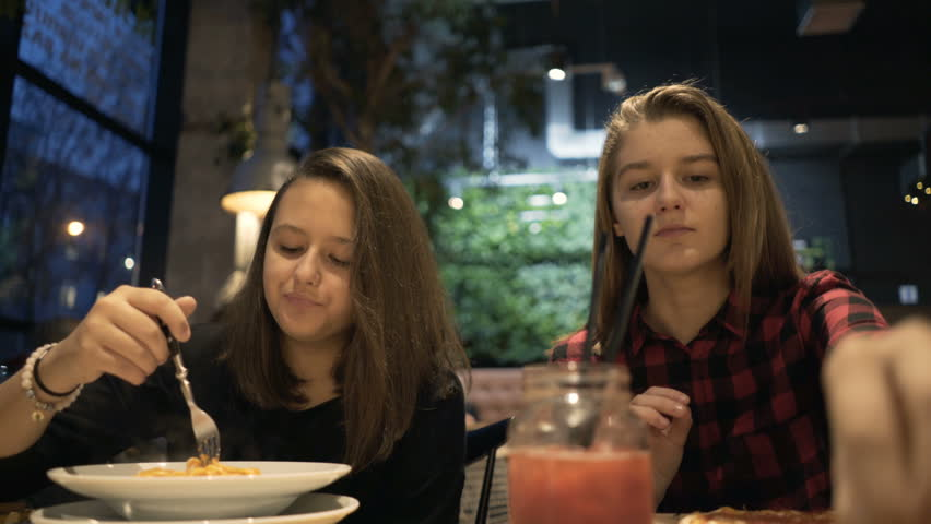 Two teenage girlfriends eating meal sitting in cafe at night