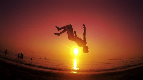 Parkour free runner runs and jumps backflip at summer beach sunset. Steadicam SLOW MOTION shot