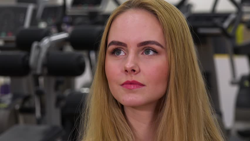 A young beautiful woman looks around in a gym - face closeup | Shutterstock HD Video #1009455992