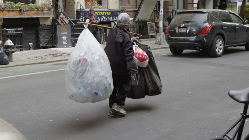 NEW YORK - MAY 17, 2015: homeless Asian lady carrying plastic bags filled with empty soda cans, slow motion 4K Manhattan NY. Homelessness is a major problem in New York City, USA.