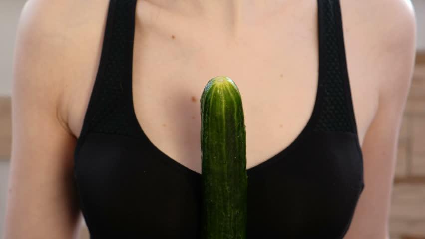 Closeup woman's hands dress the condom on cucumber.
