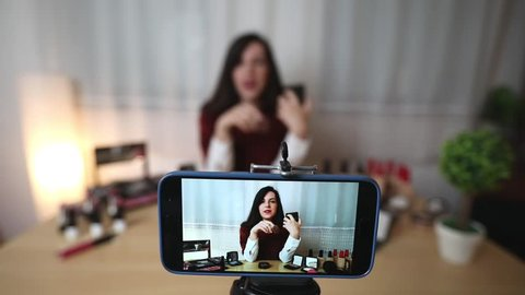 SLOW MOTION: Makeup vlogger influencer creating cosmetic product explainer video. Young woman is filming a new episode for her personal make up vlog. Recording live tutorial video on smart phone.