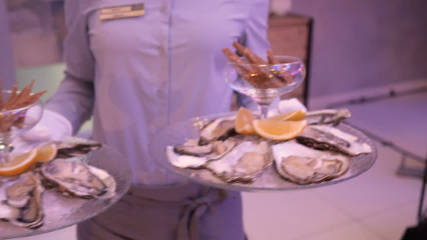 The waiter carries oysters on round transparent trays, oysters on ice with slices of lemon and in the middle of the plate a bowl with a long leg with croutons from bread, a beautiful dish in the