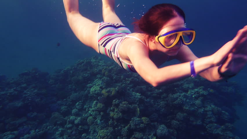 Girl dive in Red sea near coral reef with wish, underwater slow motion