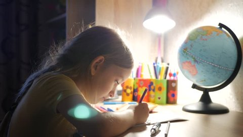 Young mother helps her daughter with her homework at on the table under the light of a lamp. Mom holds a small son in his arms.