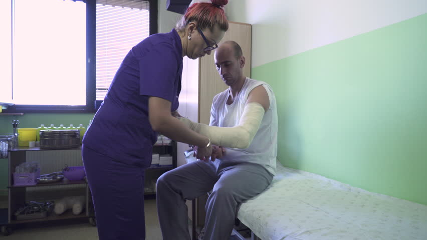 Nurse in purple uniform bandaging male patient injured hand while he sitting on hospital bed, middle age female medical technician wrapping bandage on arm of man in clinic room, steadicam, dolly shot.