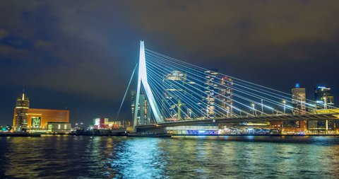 Timelapse of Rotterdam cityscape and Erasmus bridge over Nieuwe Maas in the night illuminated. Rotterdam, Netherlands. Zoom out effect