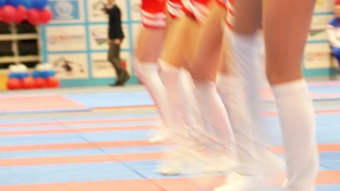 Attractive cheerleaders in red dresses dancing at the karate championship