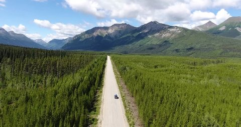 A van is driving on an empty wild street in the middle of nowhere