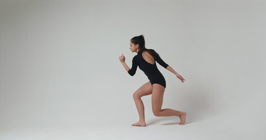 Young sensual fit woman wearing black bodysuit practicing dance in spacious bright room.