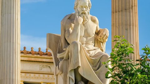 Statue of the great Greek philosopher Socrates on a marble chair, background of columns and sky, time lapse.