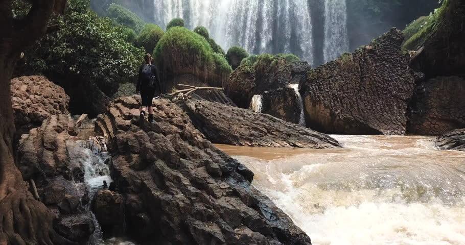 Tourist traveller walking at Elephant Waterfall below in trip in Vietnam, woman enjoying beauty of nature