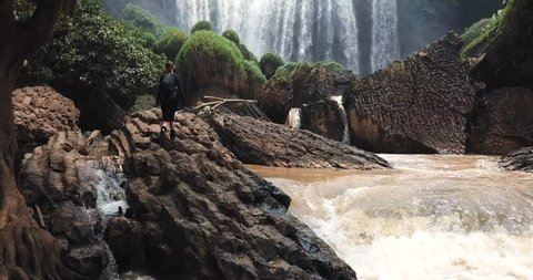 Tourist traveller walking at Elephant Waterfall below in trip in Vietnam, woman enjoying beauty of nature