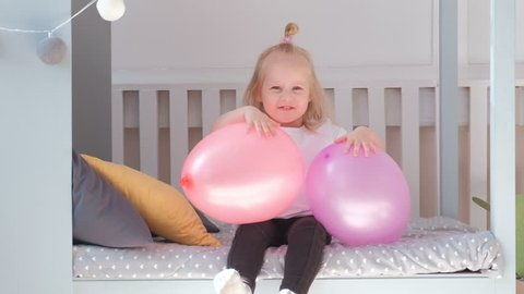 Little charming blond girl sitting on bed in her room with pink balloons and smiling.