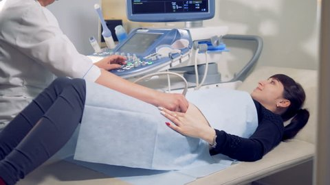 Gynecologist is carrying out an ultrasound procedure on a female patient