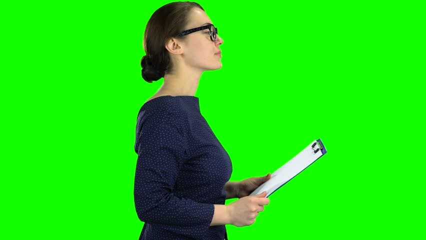 Business lady comes with a paper tablet on the street. Green screen. Side view