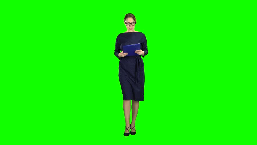 Business lady comes with a paper tablet on the street. Green screen