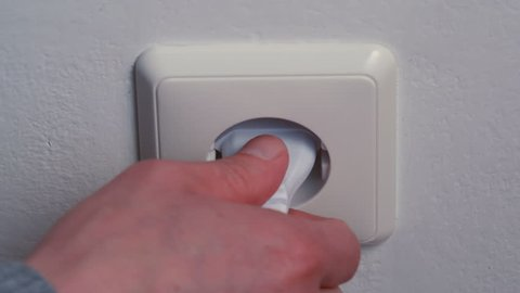 Hand puts a power plug in the wall socket