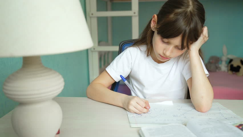 Girl tired of doing lessons. Bored schoolgirl day writing | Shutterstock HD Video #1009732742