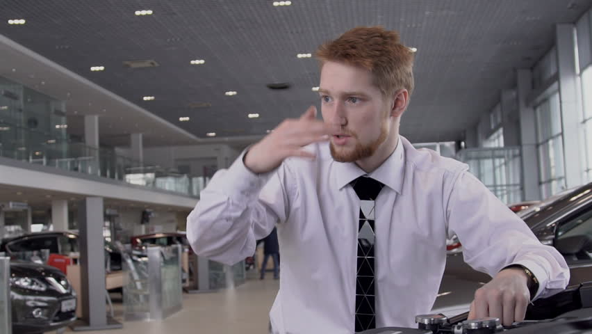 In showroom red-haired bearded consultant man in white shirt talks about advantages of an expensive vehicle purchase with discount on store. slow motion. Concept: sales consultant, car dealership | Shutterstock HD Video #1009742972