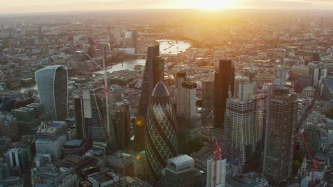 London UK - November 2017: Aerial view at sunset with sun flare London cityscape financial district modern skyscrapers Gherkin Cheesegrater England United Kingdom RED WEAPON