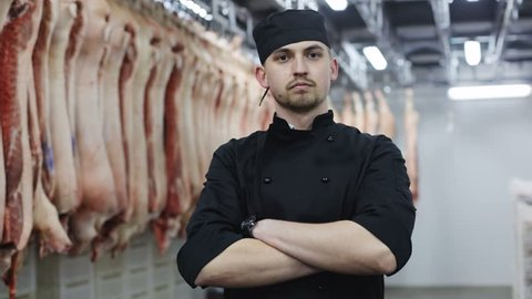 Portrait of young confident male butcher crossing arms while standing by meat hanging in slaughterhouse manufacturing factory man wearing modern black uniform successful food business slaughtering