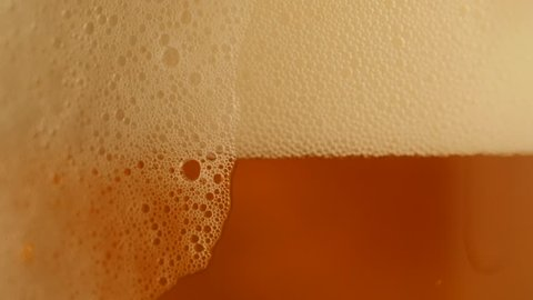 Pouring fresh beer with foam running down, slowmotion footage