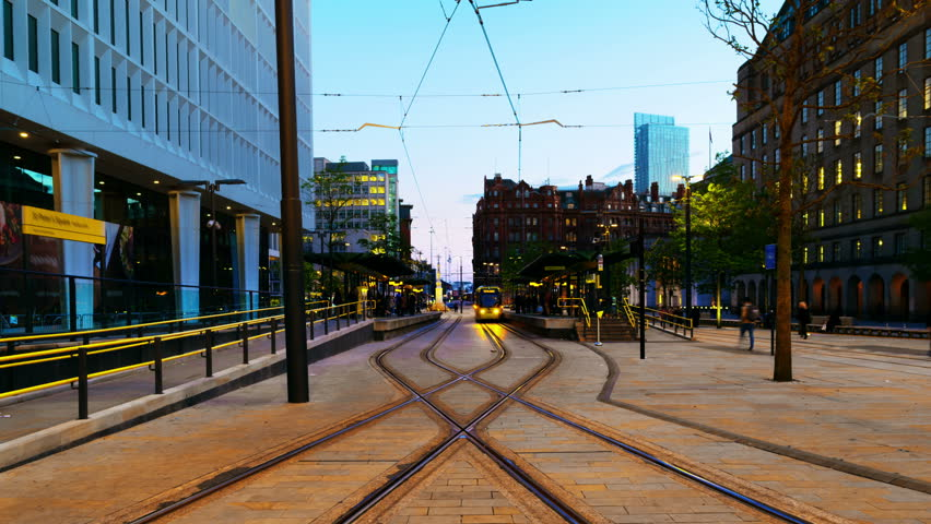 Manchester, England. Light rail yellow tram in city center of Manchester, UK in the evening. Time-lapse from day to night with illumination