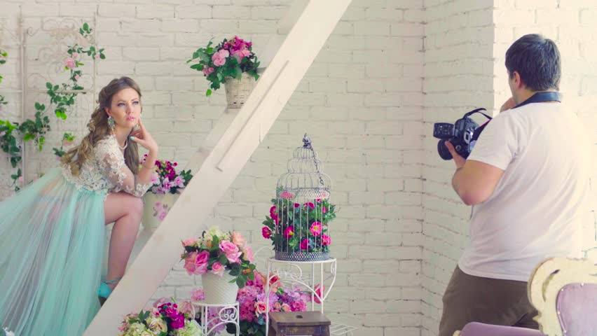 Beautiful model in peignoir posing against white brick wall surrounded by baskets of flowers. Photographer taking photos.