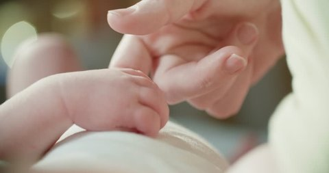 4k ,Parent holding newborns hand in Slow Motion . Happy Family Mother and her Newborn Baby together. Maternity concept. Parenthood. Motherhood. Magic light bokeh background