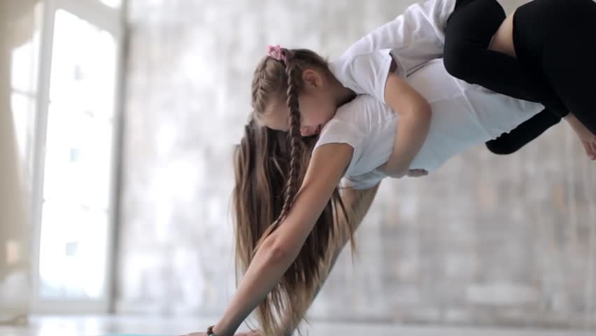 Yoga with children, mom and daughter doing stretching | Shutterstock HD Video #1009800422