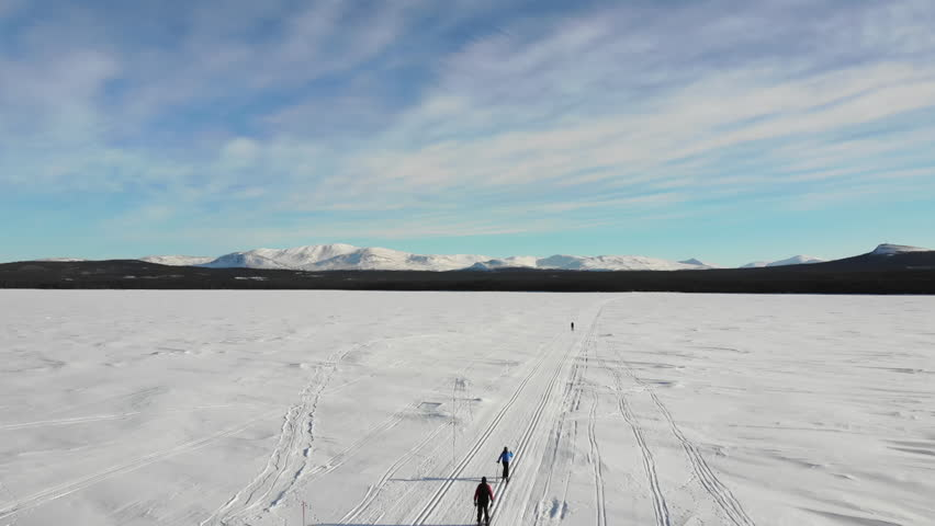 Aerial view of a a woman and a kid, cross country skiing on a lake track in the swedish mountains
