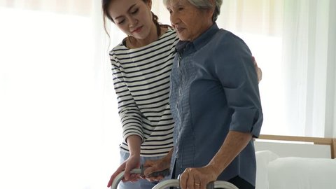 Young woman helping senior man to stand up with walker at home