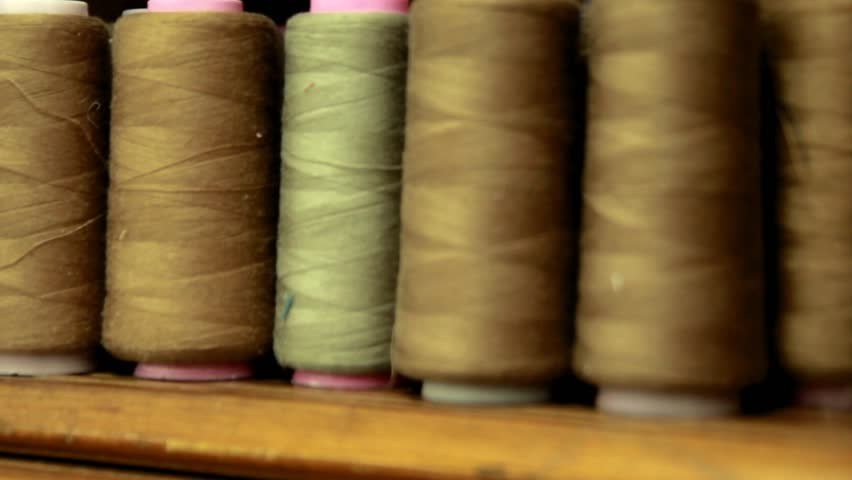 Plastic spools of high quality cotton pastel colors sewing thread, close-up. All-purpose thread spools on a sewing machine spindle.