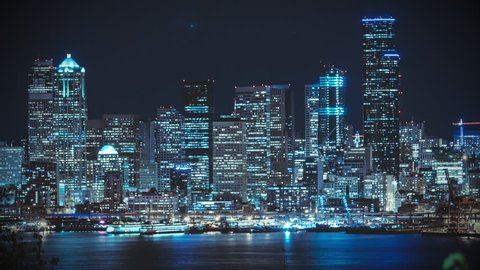 Stylized Seattle Waterfront Night Timelapse.  Flat vintage profile for high speed shot of downtown cityscape with tall skyscraper buildings illuminated by blue hue