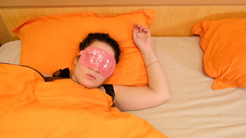 Closeup 4k video of sleeping young woman wearing blindfold mask. Wakes up and removes the bandage. Aware that he has overslept | Shutterstock HD Video #1009895342