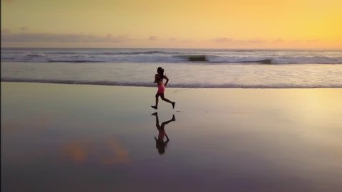 Aerial panning with drone on attractive Asian sport runner woman in running workout practice at sunset beach backlit as silhouette in fitness and healthy lifestyle concept