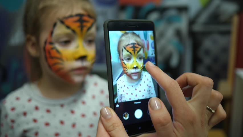 Body art painted face cute little girl on birthday theme party taking phone picture for instagram | Shutterstock HD Video #1009904252