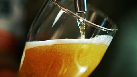 Process of pouring beer into glass beaker in grill bar.