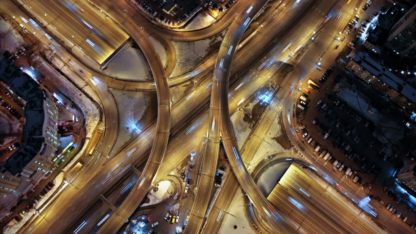 Aerial hyperlapse shooting of a busy multilevel  junction. Illuminated highway from the bird's eye view.  Car light trails at night.