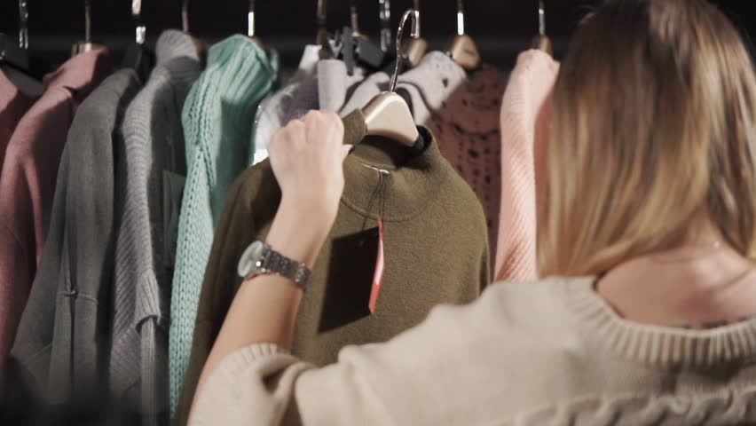 a young woman holds a warm sweater on her hanger, on which a tag with a price weighs, a lady looks at the material from which this clothing is made