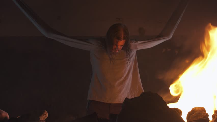 Crazy long haired caucasian man with straitjacket sleeves tied to ceiling in burning abandoned building
