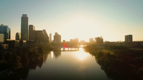 An aerial shot of a kayaker paddling along town lake in Austin, Texas at sunrise with the city in the background.